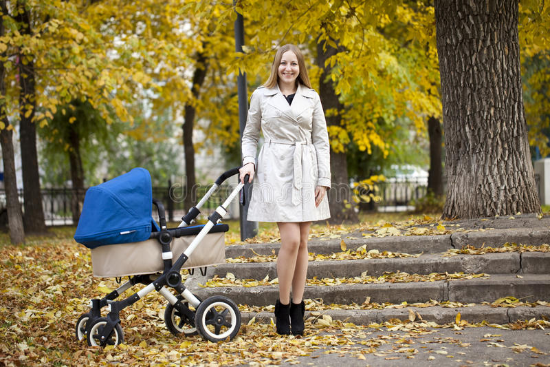 Madre con il passeggiatore di bambino per un neonato immagini stock