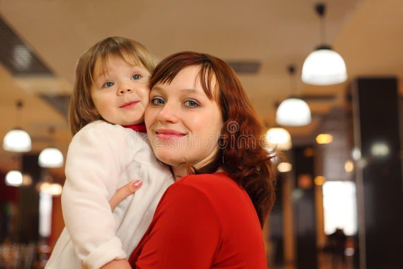 Madre con il piccolo basamento della figlia in caffè fotografie stock