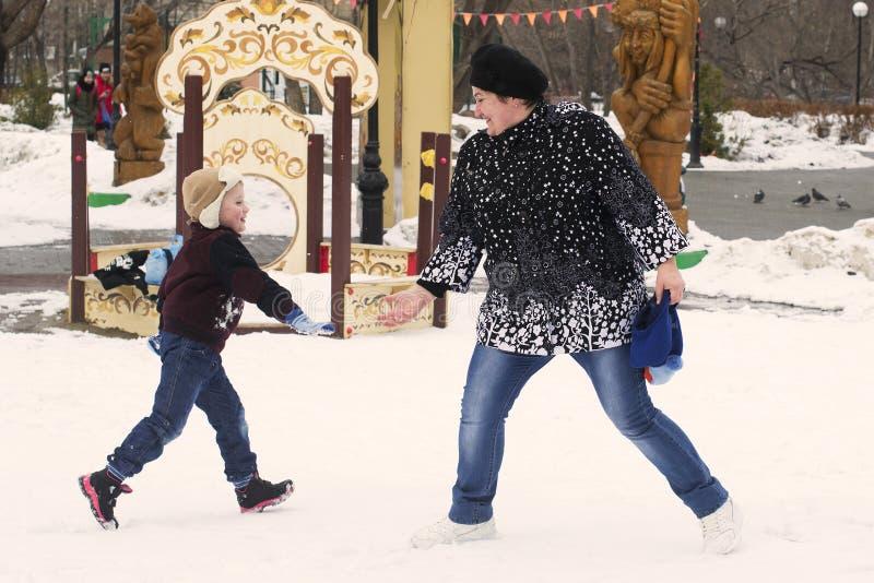 Madre con il piccolo gioco del figlio sul campo da giuoco nell'inverno fotografie stock