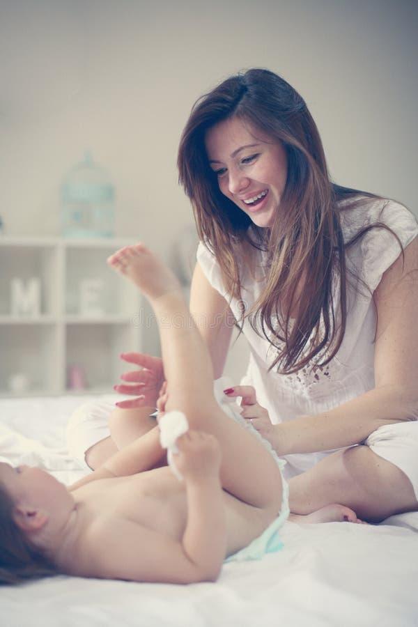 Madre con il suo bambino a casa Pannolino cambiante della madre il suo piccolo fotografie stock