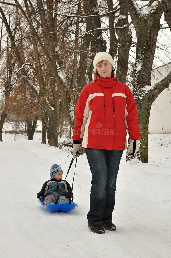 Madre con il suo bambino sulla slitta fotografia stock