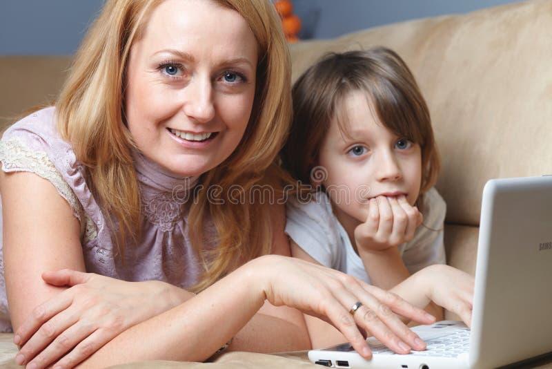 Madre con il suo lavoro del figlio sul calcolatore del netbook fotografia stock