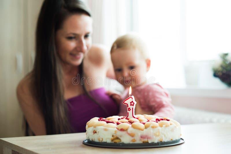 Madre con il suoi derivato e torta di compleanno svegli con la candela immagine stock