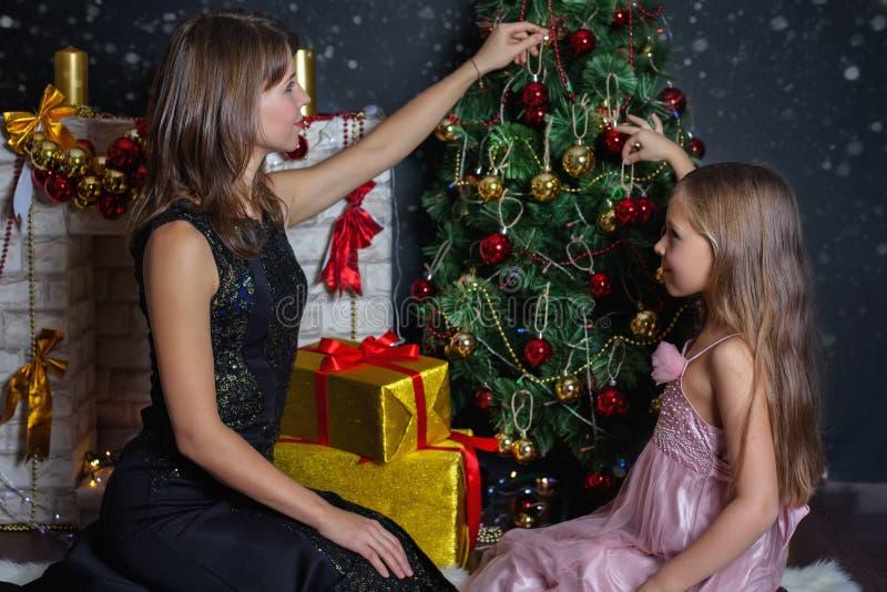 Madre con il vostro bambino che decora l'albero di Natale immagini stock libere da diritti
