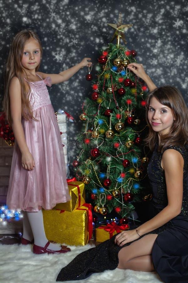 Madre con il vostro bambino che decora l'albero di Natale fotografie stock