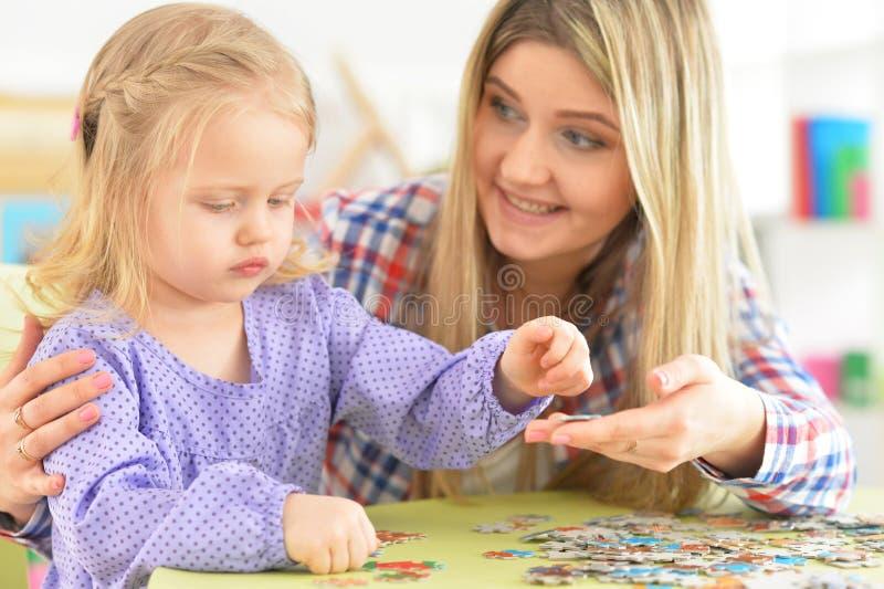 Madre con la figlia che raccoglie puzzle fotografia stock