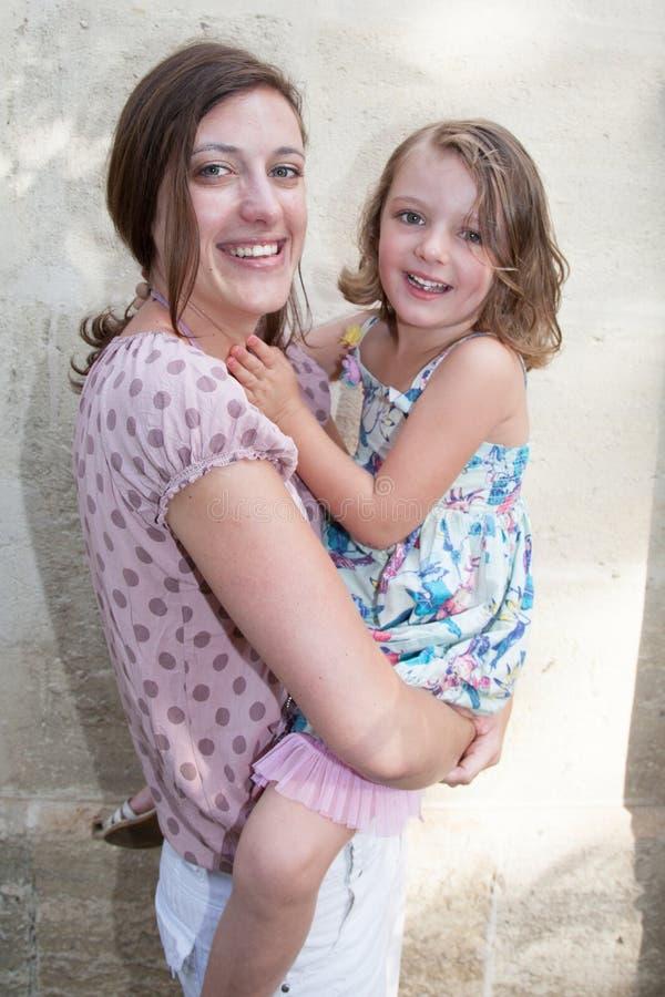 madre con la hija de la muchacha del niño en brazos al aire libre imágenes de archivo libres de regalías