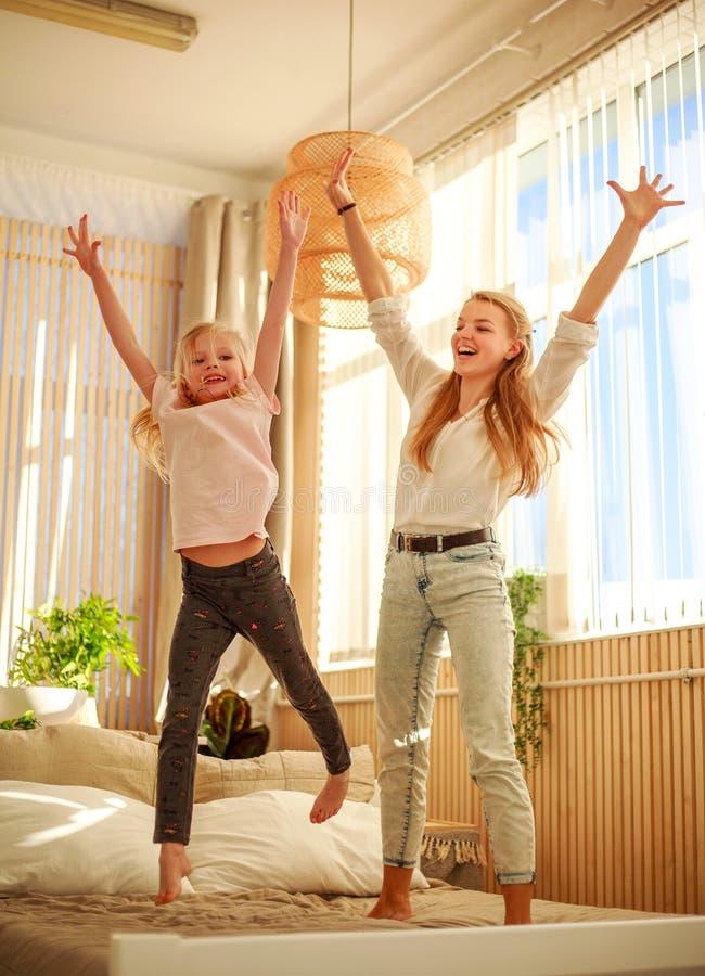 Madre con la hija del ni?o que se divierte en casa que salta en la cama, paternidad feliz imagenes de archivo