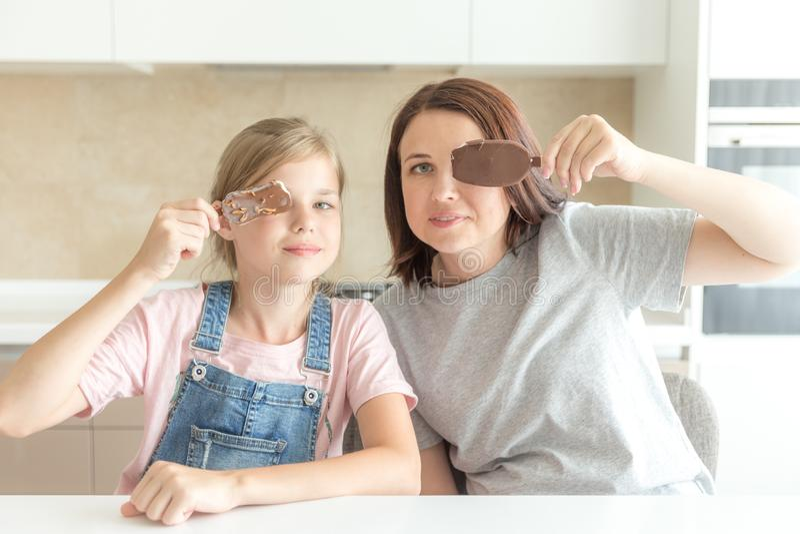 Madre con la hija en cocina que come el helado Buenas relaciones del padre y del ni?o Concepto de familia feliz fotos de archivo