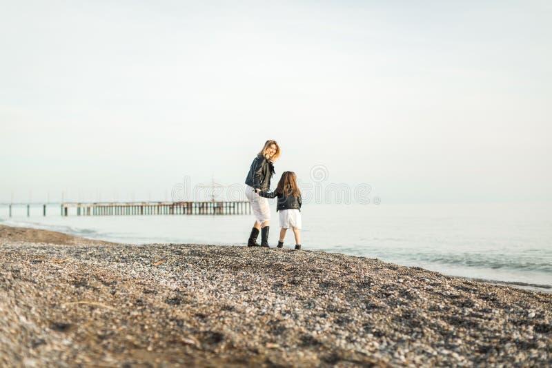 Madre con la hija que camina en el mar foto de archivo libre de regalías