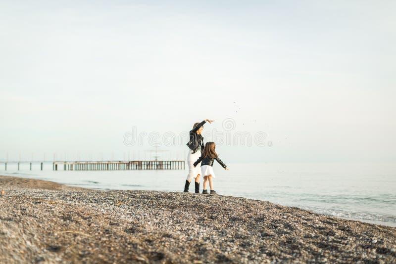 Madre con la hija que camina en el mar foto de archivo