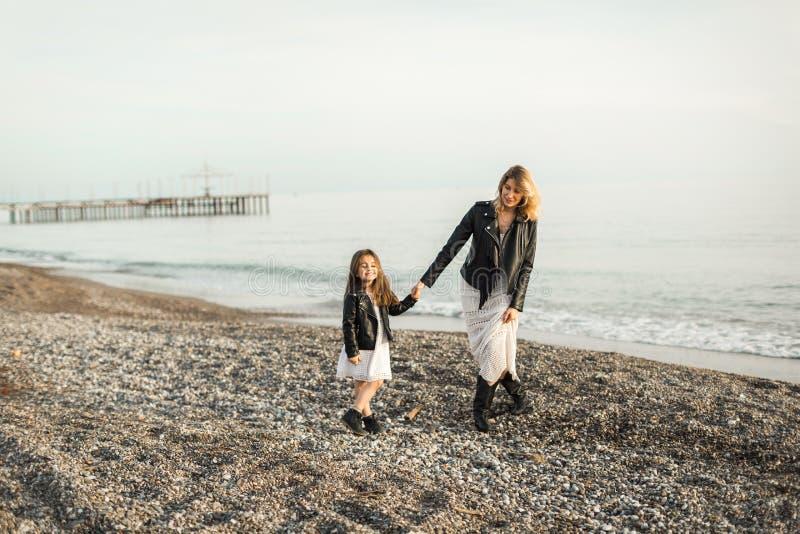 Madre con la hija que camina en el mar imagenes de archivo