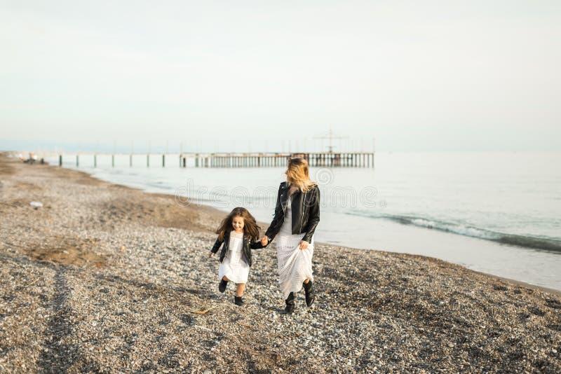 Madre con la hija que camina en el mar fotos de archivo