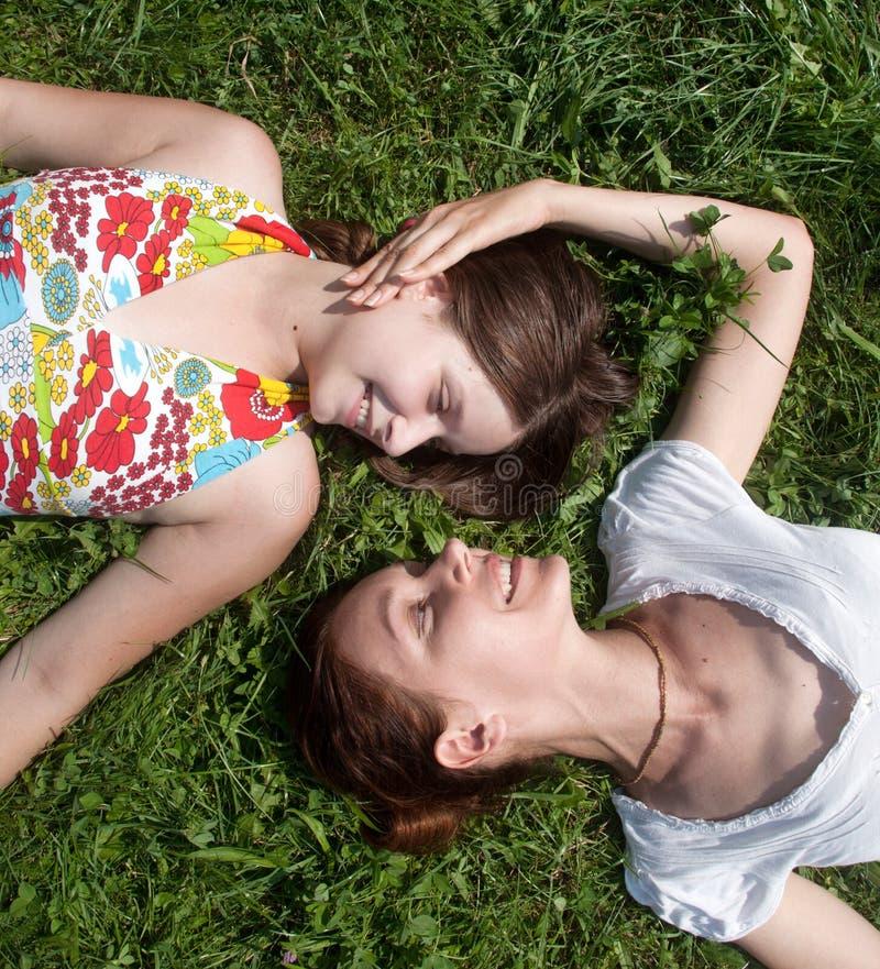 Madre con la hija que pone en una hierba en parque imagenes de archivo