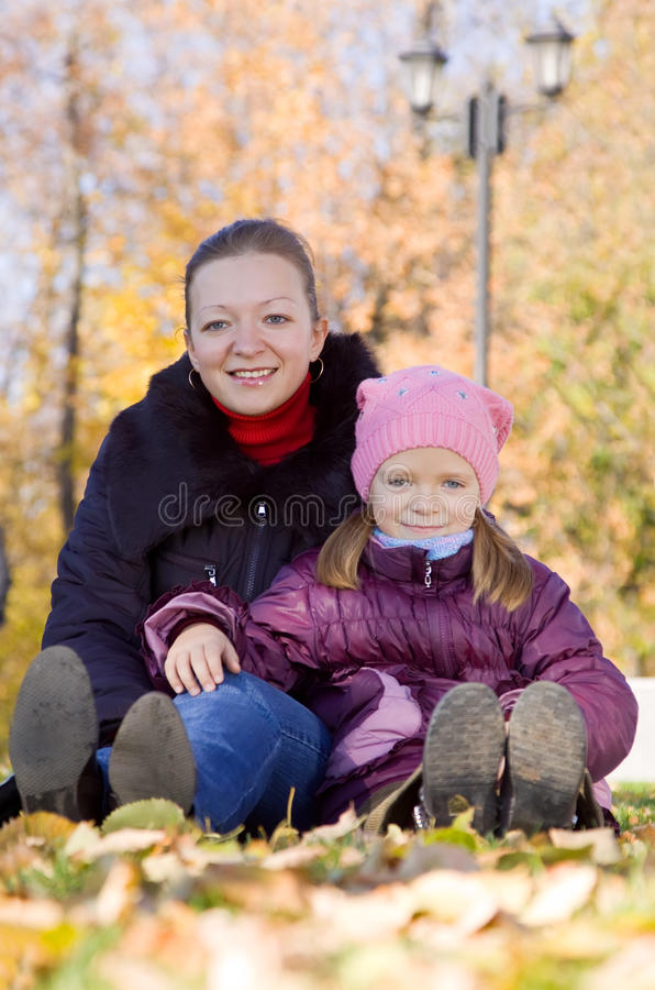Madre con la hija que se sienta en otoño imagen de archivo