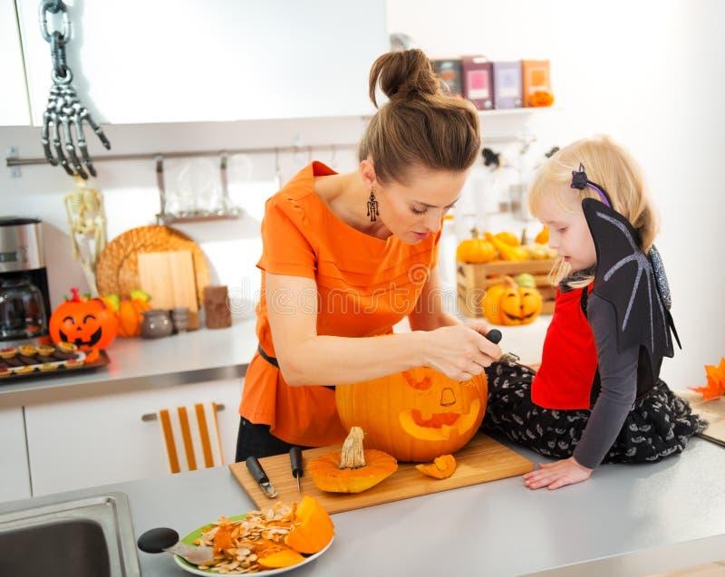 Madre con la hija que talla la Jack-O-linterna para el partido de Halloween fotos de archivo