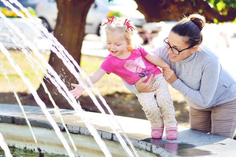 Madre con la neonata vicino alla fontana fotografia stock libera da diritti