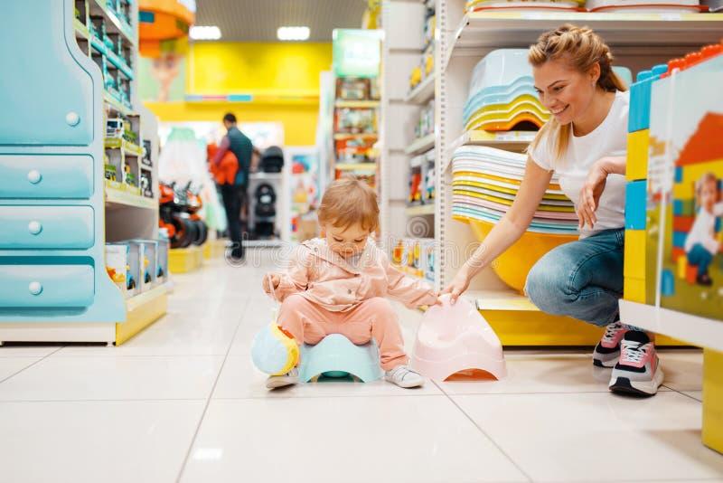 Madre con la ragazza che sceglie bambino banale nel deposito dei bambini immagini stock libere da diritti