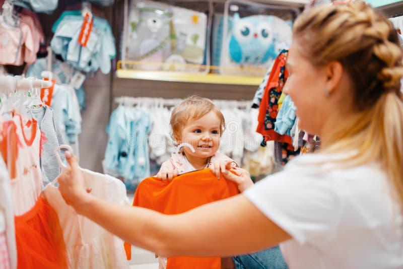 Madre con la ragazza che sceglie i vestiti nel deposito dei bambini fotografia stock