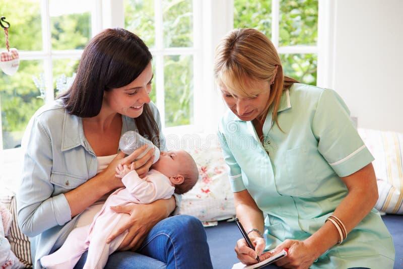 Madre con la reunión del bebé con el visitante de la salud en casa fotografía de archivo