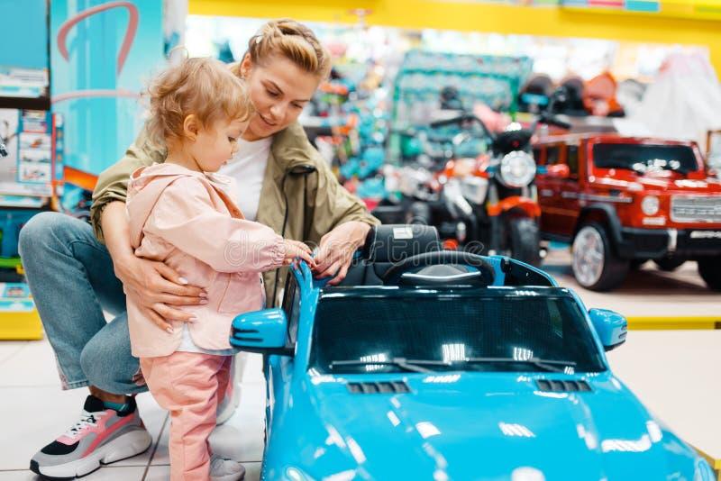 Madre con la scelta della ragazza electromobile in deposito fotografie stock