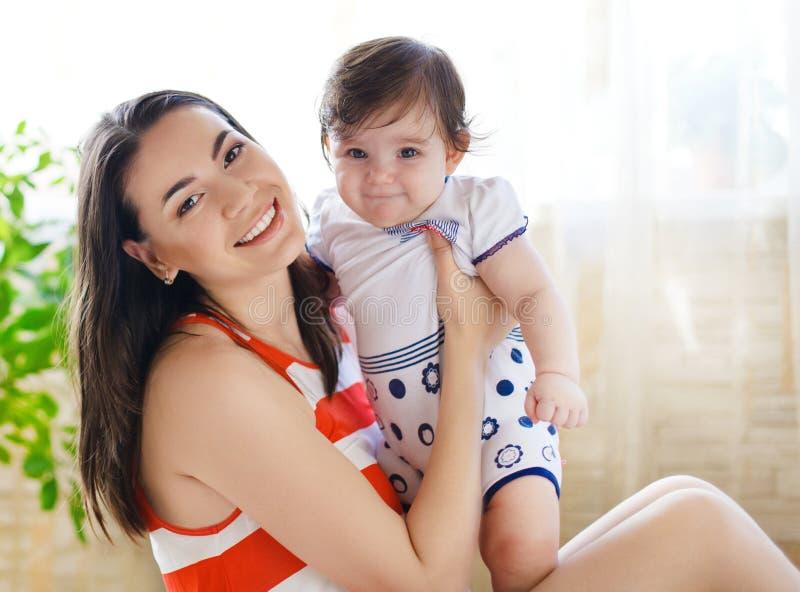 Madre con la vieja niña de ocho meses interior foto de archivo