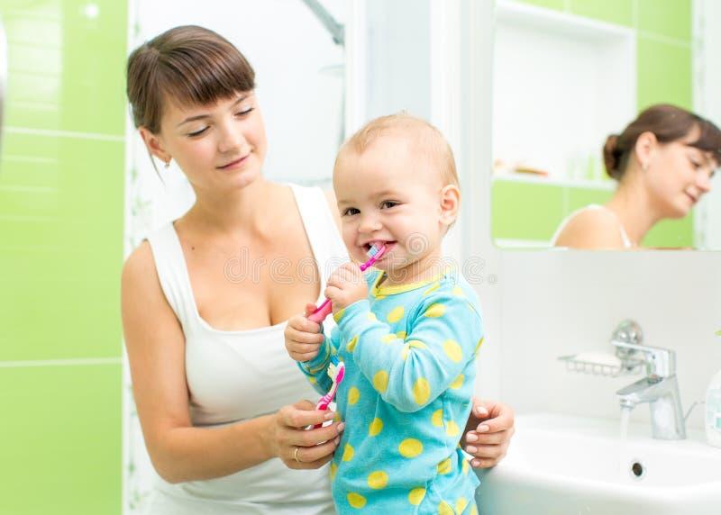 Madre con los dientes de cepillado de la muchacha del niño imagen de archivo