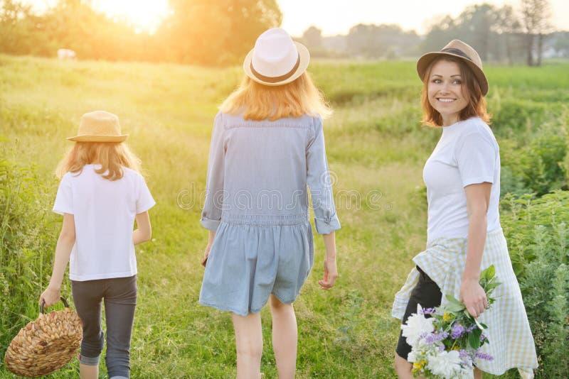 Madre con los niños dos hijas que caminan a lo largo de una carretera nacional, visión trasera fotos de archivo