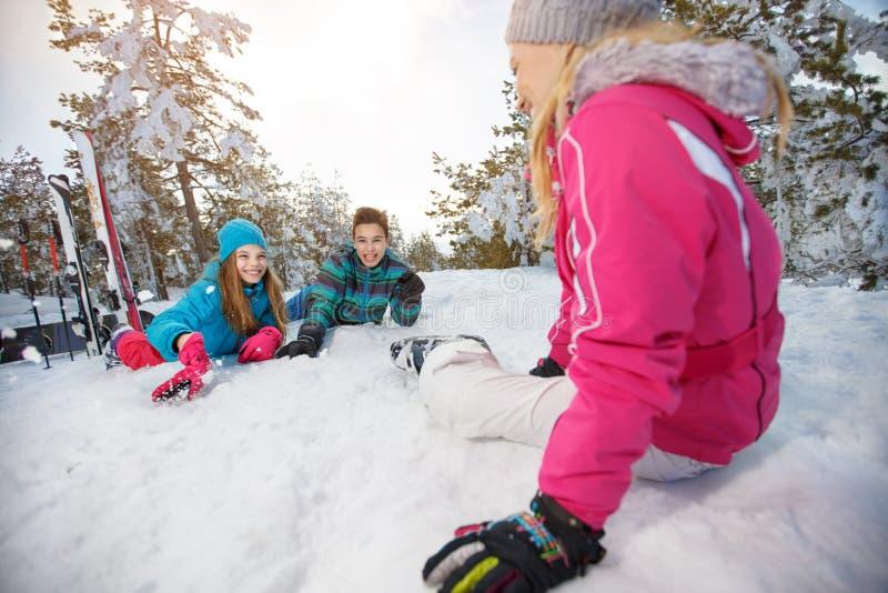 Madre con los niños en el esquí que descansa sobre nieve foto de archivo libre de regalías