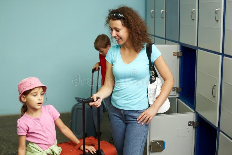 Madre con los niños en oficina del izquierdo-equipaje fotos de archivo