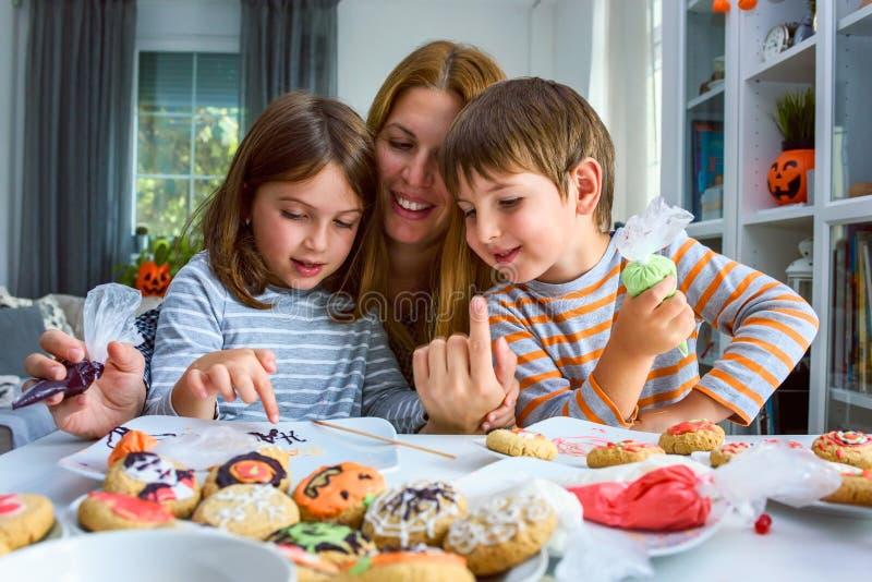 Madre con los niños que adornan las galletas para Halloween imagen de archivo