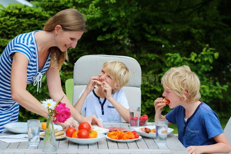 Madre con los niños que comen al aire libre imagenes de archivo