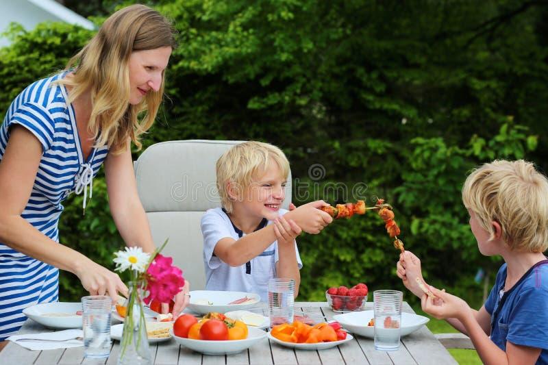 Madre con los niños que comen al aire libre imagen de archivo