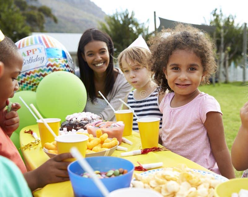 Madre con los niños que disfrutan de la fiesta de cumpleaños al aire libre junto fotos de archivo libres de regalías