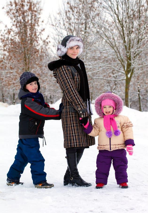 Madre con los niños que se relajan en la nieve imágenes de archivo libres de regalías
