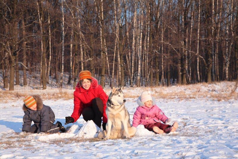 Madre con los niños y el perro en invierno imagen de archivo