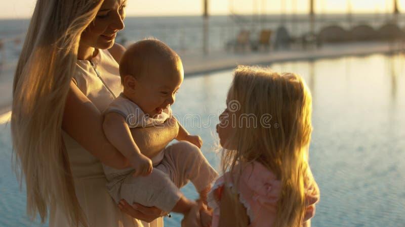 Madre con los pequeños niños que hacen una pausa la piscina en la puesta del sol imagen de archivo