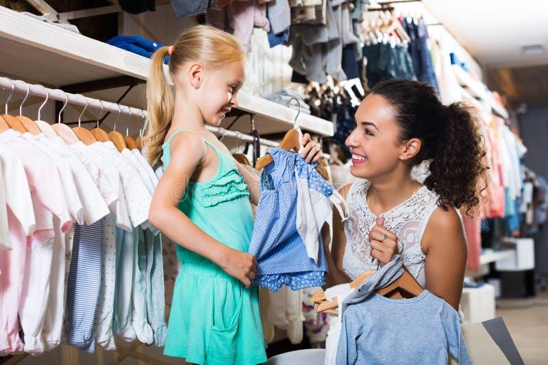 Madre con ropa de compra de la hija fotos de archivo