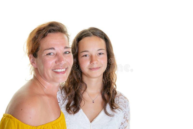 Madre con su hija adolescente que abraza y que ríe en el fondo blanco fotografía de archivo libre de regalías