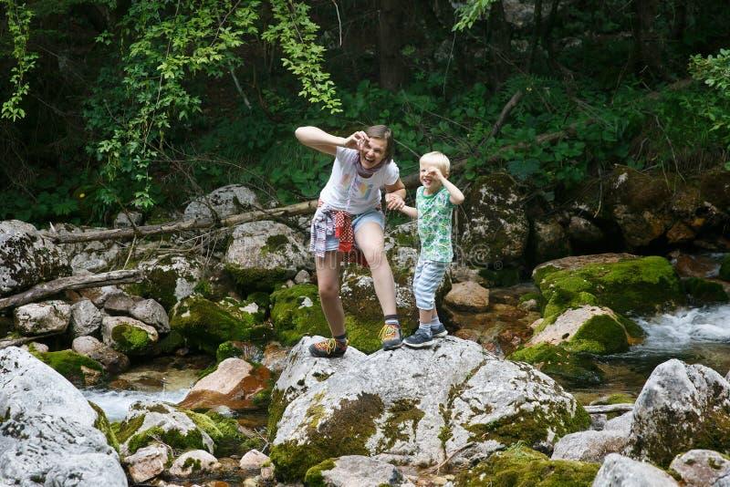 Madre con su hijo que hace caras divertidas, divirtiéndose por una corriente de la montaña en un viaje de la familia imagenes de archivo