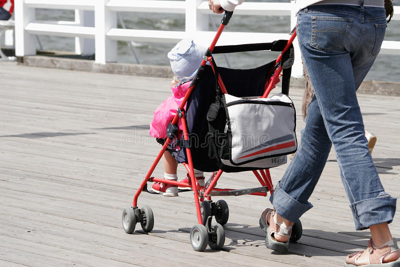 Madre con su niño en caminar del cochecito foto de archivo