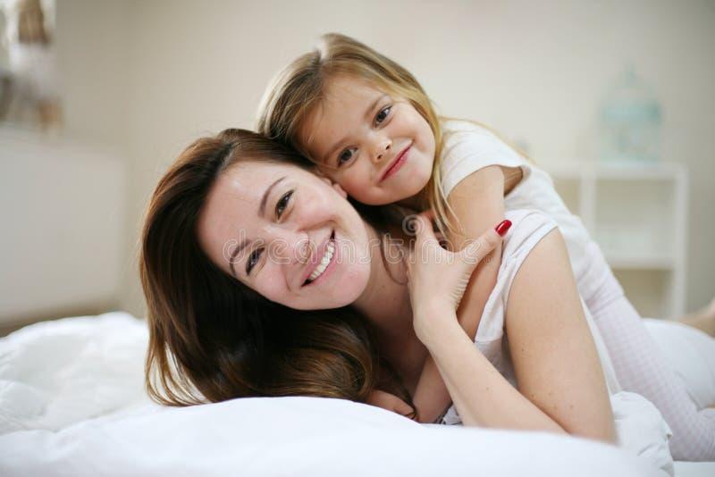 Madre con su pequeña hija linda que miente en cama foto de archivo