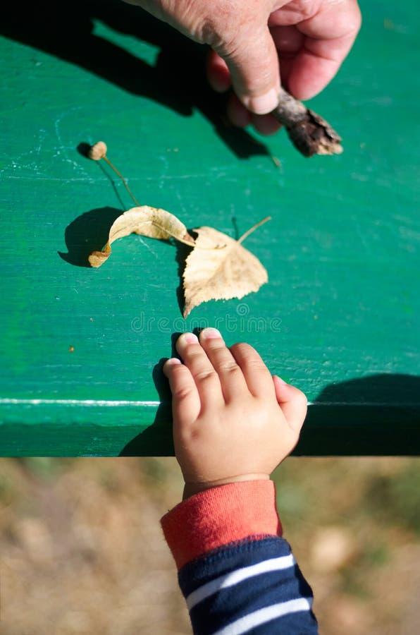 Madre con un piccolo bambino che gioca con le foglie autunnali fotografia stock