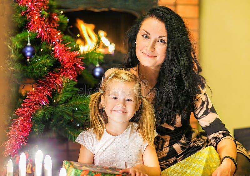 Madre con una hija Cajas de regalos en el fondo del foto de archivo