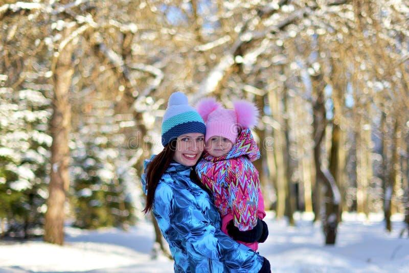 Madre con una poca hija en un paseo en el bosque en un invierno nevoso fotografía de archivo libre de regalías