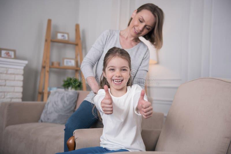 Madre contenta que se peina el pelo de las hijas imagen de archivo