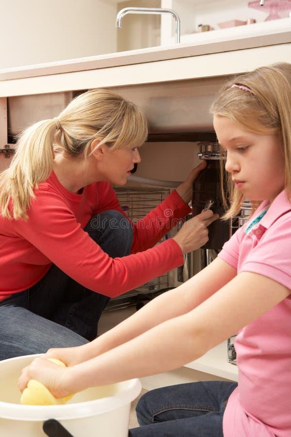 Madre d'aiuto della figlia per pulire perdita con lo straccio immagine stock libera da diritti