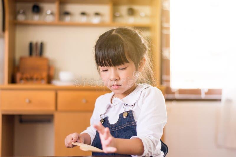 Madre d'aiuto della piccola ragazza asiatica che fa la cucina dell'alimento a casa di mattina, fine su fotografie stock