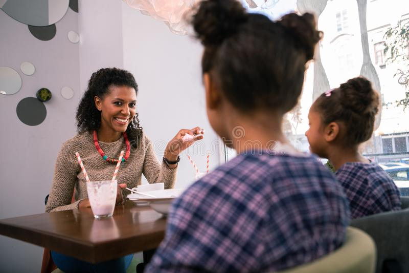 Madre d'orientamento preoccupantesi che parla con sue piccole ragazze adorabili in self-service immagini stock