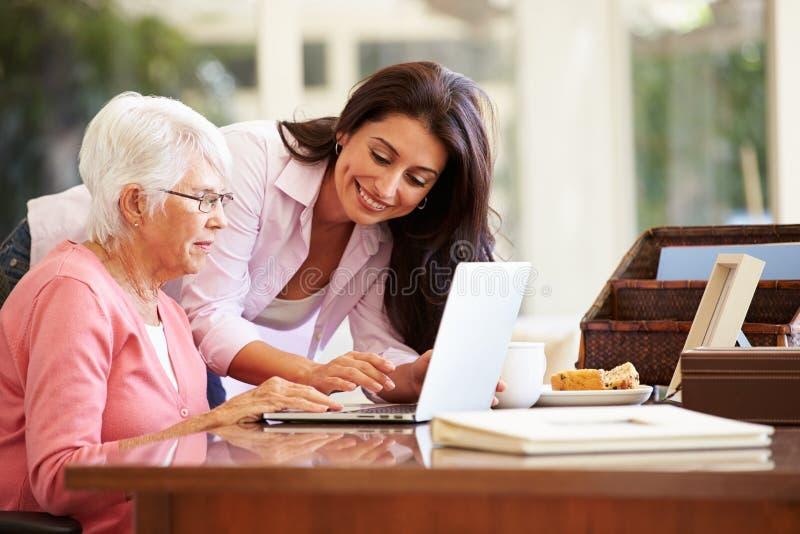 Madre de ayuda de la hija adulta con el ordenador portátil foto de archivo